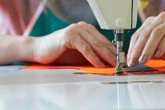 Plan rapproché des affaires du ` s de tailleur - mains femelles derrière sa couture Images libres de droits