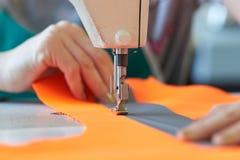 Plan rapproché des affaires du ` s de tailleur - mains femelles derrière sa couture Photographie stock libre de droits