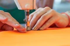 Plan rapproché des affaires du ` s de tailleur - mains femelles derrière sa couture Photos libres de droits