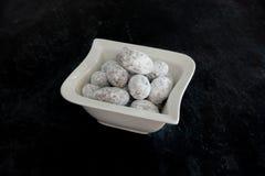 Plan rapproché des amandes recouvertes de chocolat dans une cuvette Photos stock