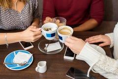 Plan rapproché des amis ayant le café à un café Photos stock