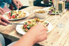 Plan rapproché des amis dînant extérieur Images stock