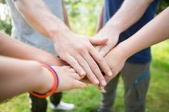 Plan rapproché des amis empilant des mains dans la forêt Photographie stock