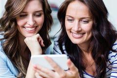 Plan rapproché des amis féminins gais à l'aide du téléphone portable Photos libres de droits