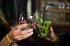 Plan rapproché des amis grillant des verres de cocktail Photo stock