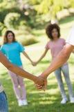 Plan rapproché des amis tenant des mains en parc Photos libres de droits