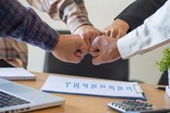 Plan rapproché des associés faisant la pile des mains lors de la réunion, Te photographie stock libre de droits