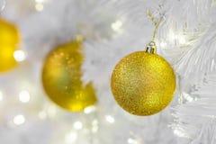 Plan rapproché des babioles d'or de Noël sur les branches blanches Photos stock