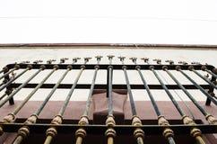 Plan rapproché des barres sur une vieille fenêtre, couleurs pourpres avec beige et blanc, fond d'une vieille maison abandonnée photographie stock