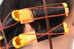 Plan rapproché des bigoudis jaunes dans les cheveux Image stock