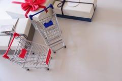 Plan rapproché des boîte-cadeau et du caddie sur le bureau blanc photographie stock