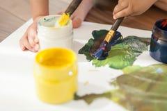 Plan rapproché des boîtes avec des peintures, des brosses et des mains du ` s d'enfants photo stock