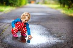 Plan rapproché des bottes de pluie de petite fille d'enfant en bas âge et des pantalons et de la marche de port pendant le vergla image libre de droits