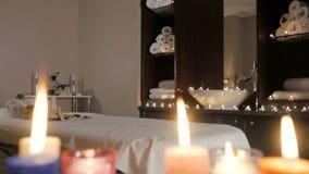 Plan rapproché des bougies brûlantes écartant l'arome sur la table dans une salle de station thermale banque de vidéos