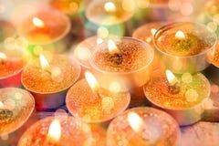 Plan rapproché des bougies brûlant sur la planche en bois Photos stock