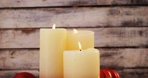 Plan rapproché des bougies brûlantes avec la décoration de Noël sur la planche en bois banque de vidéos