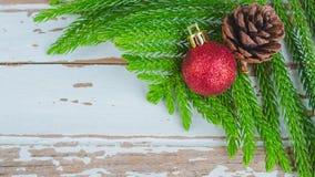 Plan rapproché des boules de Noël et des cônes rouges de pin sur en bois Photos stock