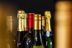 Plan rapproché des bouteilles de vin dans un espace de chambre noire pour le texte Images stock