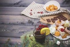 Plan rapproché des brindilles impeccables bleues, biscuits de pain d'épice, bâtons de cannelle, tranches des meringues oranges et images stock