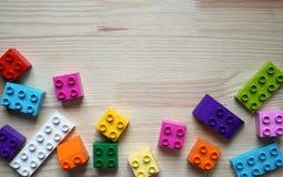 Plan rapproché des briques colorées de jouet, sur un fond en bois photographie stock