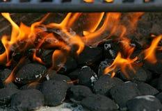 Plan rapproché des briquettes et des flammes de charbon de bois photographie stock