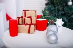 Plan rapproché des cadeaux de Noël sur une table devant un arbre de Noël images stock