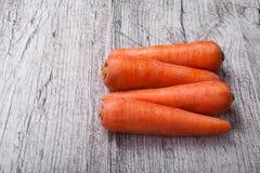 Plan rapproché des carottes oranges, légumes complètement de carotène pour les smoothies sains et sains sur un fond en bois clair photos stock