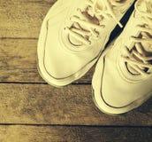 Plan rapproché des chaussures blanches de sport sur le fond en bois tonalité Healt Photos libres de droits