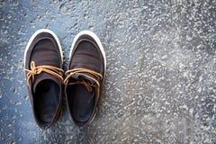 Plan rapproché des chaussures de Brown sur le fond de terrain difficile Photographie stock libre de droits