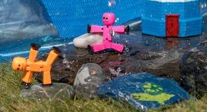 Plan rapproché des chiffres de bâton de jouet jouant sur les roches humides en soleil d'été image stock