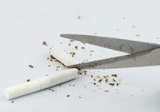 Plan rapproché des ciseaux coupant la cigarette photo stock