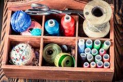 Plan rapproché des ciseaux, de l'aiguille et des fils dans la boîte en bois Images stock