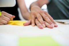 Plan rapproché des collègues de bureau avec la main en main au bureau Image stock