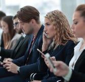 Plan rapproché des collègues s'asseyant à une conférence d'affaires Photos libres de droits