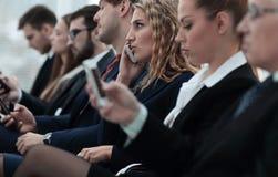 Plan rapproché des collègues s'asseyant à une conférence d'affaires Photo libre de droits