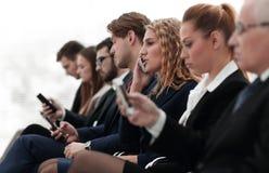 Plan rapproché des collègues s'asseyant à une conférence d'affaires Photos stock