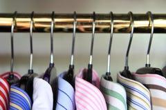 Plan rapproché des colliers du men& x27 ; chemises de s accrochant sur un rail Images libres de droits