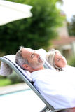 Plan rapproché des couples détendant dans de longues chaises Image stock