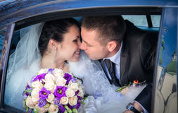 Couples de nouveaux mariés embrassant dans le véhicule de mariage Image libre de droits