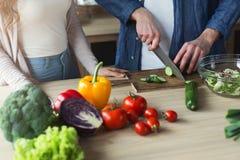Plan rapproché des couples faisant cuire la nourriture saine ensemble Photos stock