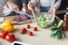 Plan rapproché des couples faisant cuire la nourriture saine ensemble Photo stock