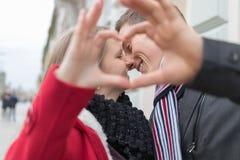 Plan rapproché des couples faisant la forme de coeur avec des mains Horaire d'hiver Images stock