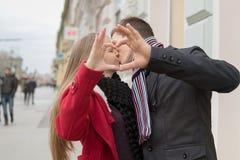 Plan rapproché des couples faisant la forme de coeur avec des mains Horaire d'hiver Photo libre de droits