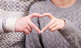 Plan rapproché des couples faisant la forme de coeur avec des mains Image stock