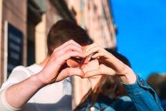 Plan rapproché des couples faisant la forme de coeur avec des mains et des baisers Photos libres de droits