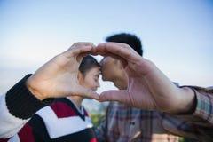 Plan rapproché des couples faisant la forme de coeur avec des mains, heureux dans l'amour photo libre de droits