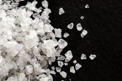Plan rapproché des cristaux de sel brut sur le noir images libres de droits