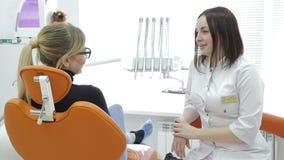 Plan rapproché des dents de examen du ` s de jeune femme de dentiste banque de vidéos