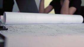 Plan rapproché des dessins de construction professionnels barre Rouleau de mensonges de papier sur la table avec des dessins de c banque de vidéos