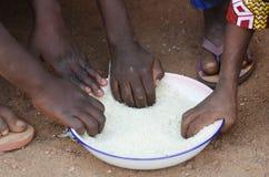 Plan rapproché des enfants africains mangeant un repas dehors Images stock